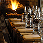 a long table is set at a restaurant by the fire